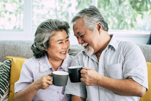 Elderly couple on couch with smiles drinking from mugs